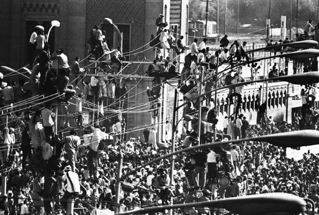 Egyptians crowd the tops of telegraph poles in Cairo, Egypt on October 1, 1970, for a grandstand view of President Gamal Abdel Nasser's funeral procession. (Photo by Eddie Adams/AP Photo)