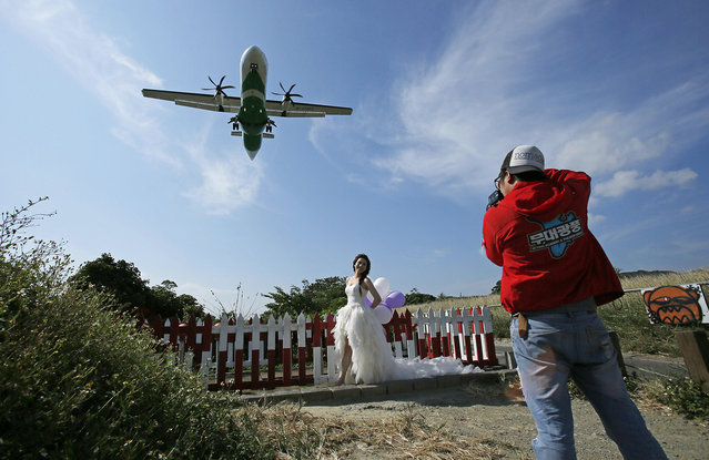 A bride has her wedding photos taken under the flight path at Songshan airport in Taipei, Taiwan, Thursday, October 30, 2014. (Photo by Wally Santana/AP Photo)