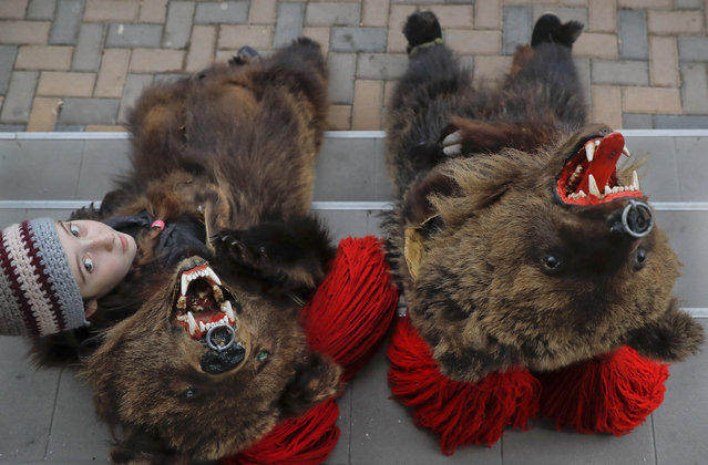 In this Saturday, December 30, 2017, picture, Cleopatra Antonia Turcu, 10 years-old, wearing a bear fur costume pauses next to Georgiana Andresoaie, during an annual bear parade in Comanesti, Romania. The tradition, originating in pre-Christian times, when dancers, wearing colored costumes or animal furs, went from house to house in villages singing and dancing to ward off evil, has moved to Romania's cities, where the ritual is performed for money. (Photo by Vadim Ghirda/AP Photo)