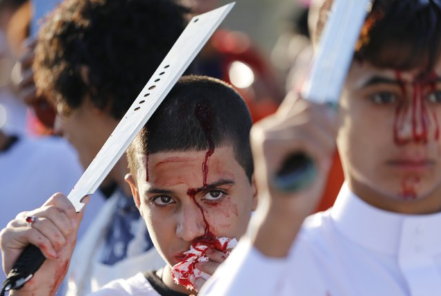 Iraqi Shi'ite Muslims bleed after hitting their foreheads with swords and beating themselves as they commemorate Ashoura in Baghdad, November 4, 2014. (Photo by Thaier Al-Sudani/Reuters)