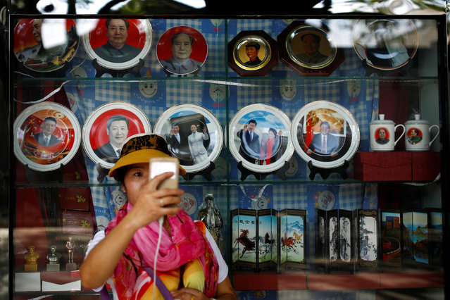 A woman takes a selfie in front of souvenirs featuring portraits of China's late Chairman Mao Zedong and China's President Xi Jinping outside a shop near the Forbidden City in Beijing, China, September 9, 2016. (Photo by Thomas Peter/Reuters)