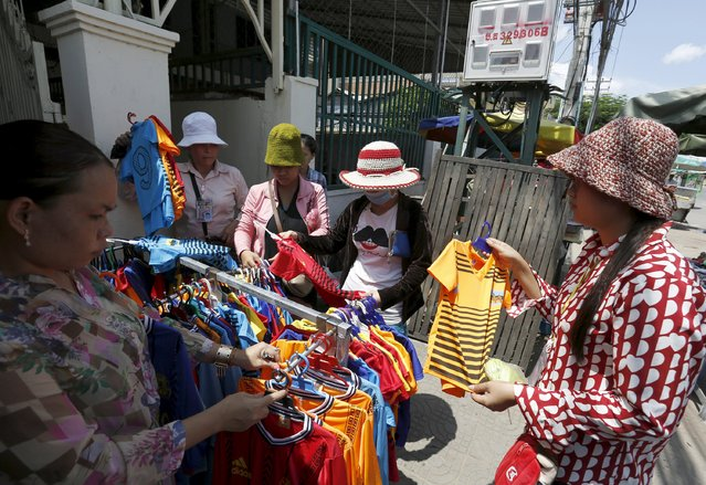 Garment workers look at shirts at a clothing stall after their lunch time in Phnom Penh October 8, 2015. (Photo by Samrang Pring/Reuters)