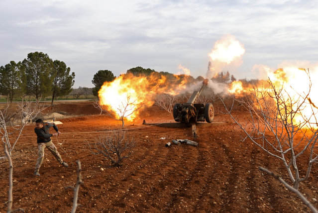 An opposition fighter fires a gun from a village near al-Tamanah during ongoing battles with government forces in Syria's Idlib province on January 11, 2018. The regime hopes to seize control of southeast parts of Idlib province to secure a main road between the capital Damascus and the northern city of Aleppo. (Photo by Omar Haj Kadour/AFP Photo)