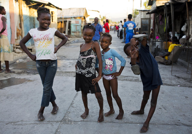 Children pose for a picture in the Cite Soleil slum of Port-au-Prince, Haiti, on December 27, 2017. (Photo by Dieu Nalio Chery/AP Photo)