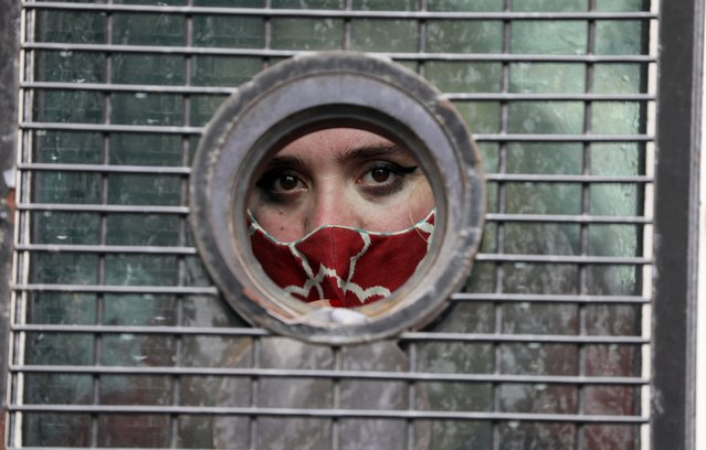 A woman is seen through the window of a police van after being detained during a protest against gender based violence outside the parliament in Cape Town, South Africa, August 29, 2020. (Photo by Sumaya Hisham/Reuters)
