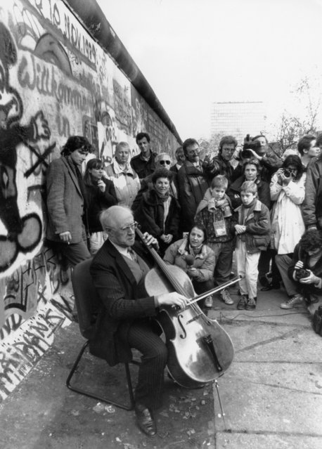 Russian cellist and composer Mstislav Rostropovich is filmed by media as he plays Bach next to the Berlin wall at Checkpoint Charlie, November 12, 1989. (Photo by Reuters/Stringer)
