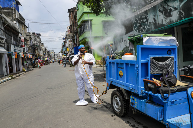 A civic worker sprays sanitizers in front of roadside shops in Kolkata, India, Sunday, August 30, 2020. (Photo by Bikas Das/AP Photo)