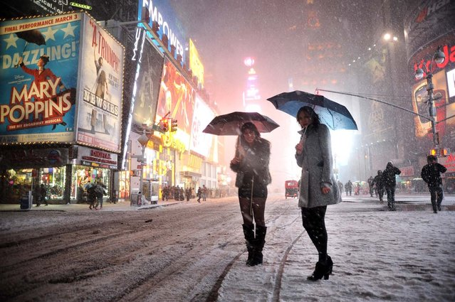 """Two girls look for a taxi in the snow in Times Square in New York on February 8, 2013 during a storm affecting the northeast US. The storm was forecast to bring the heaviest snow to the densely-populated northeast corridor so far this winter, threatening power and transport links for tens of millions of people and the major cities of Boston and New York. New York and other regional airports saw more than 4,500 cancellations ahead of what the National Weather Service called """"a major winter storm with blizzard conditions"""" along most of the region's coastline. (Photo by Mehdi Taamallah/AFP Photo)"""