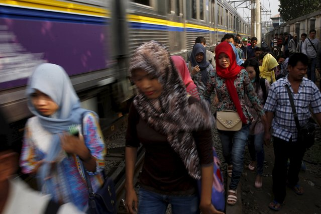 Indonesian workers walk on train tracks as they go to work at Tanah Abang train station in Jakarta, October 15, 2015. Indonesian manufacturers cut payroll numbers at the second-fastest pace in at least four years in September as industry activity contracted for a 12th straight month, the latest Nikkei Markit purchasing managers' index (PMI) survey showed. (Photo by Reuters/Beawiharta)