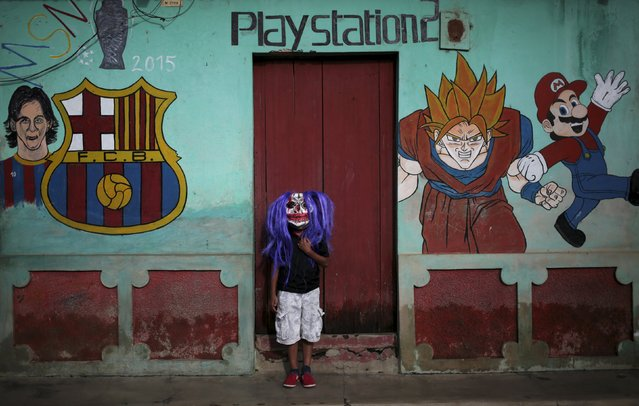 """A child wearing a mask poses for a photo in the indigenous community of Monimbo in Masaya, Nicaragua, October 16, 2015. People prepare to participate in the popular annual festival called """"The Aguizotes"""" held on the last Friday of October, where residents dress up as characters from legends and folklore mythology of Nicaragua. (Photo by Oswaldo Rivas/Reuters)"""