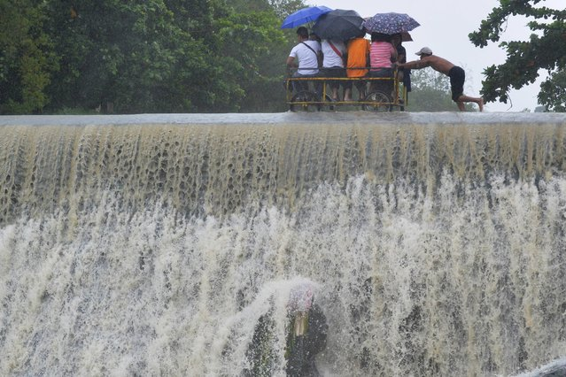 Residents cross a swelling dam, due to rising waters brought about by Typhoon Koppu, in Las Pinas city, metro Manila October 19, 2015. (Photo by Ezra Acayan/Reuters)