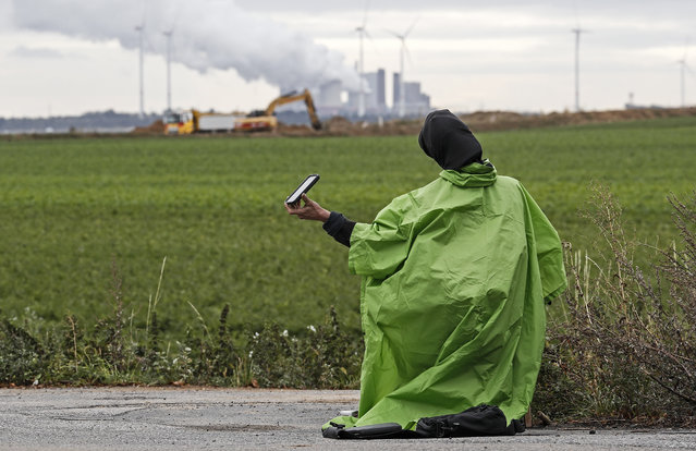 """A climate activists holds a vigil at the Garzweiler surface coal mine near Keyenberg, Germany, Friday, September 25, 2020. Several groups like """"Friday for Future"""" or """"Ende Gelaende"""" started actions for climate justice in the coming days throughout Germany. The movement demands that the German government phase out coal by 2030 and make Germany carbon neutral by 2035. (Photo by Martin Meissner/AP Photo)"""