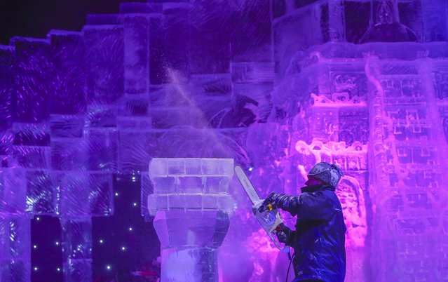A sculptor carves an ice sculpture at the Disney Dreams Ice Festival in Antwerp November 27, 2014. (Photo by Yves Herman/Reuters)