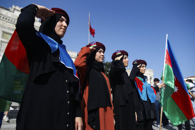 Demonstrators, wearing Turkish and Azerbaijani flags, saulte during a protest supporting Azerbaijan, in Istanbul, Sunday, October 4, 2020. Armenian and Azerbaijani forces continue their fighting over the separatist region of Nagorno-Karabakh, following the reigniting of a decades-old conflict. Turkey, which strongly backs Azerbaijan, has condemned an attack on Azerbaijan's second largest city Gence and said the attack was proof of Armenia's disregard for law. (Photo by Emrah Gurel/AP Photo)