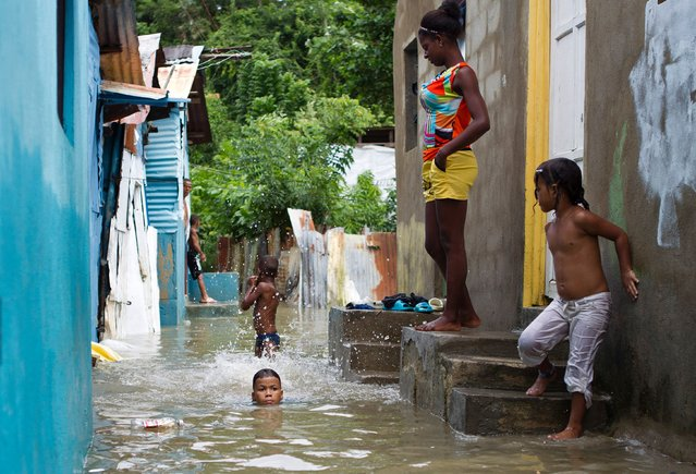 Children are pictured in the flooded neighborhood of La Puya, in Santo Domingo on October 4, 2016 after the passage of Hurricane Matthew through Hispaniola – the island that the Dominican Republic shares with Haiti. Matthew, a Category Four hurricane, slammed into the Dominican Republic and Haiti Tuesday, triggering major floods and forcing thousands to flee the path of the storm that has claimed at least three lives in each country. (Photo by Erika Santelices/AFP Photo)