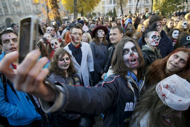 A reveller takes a selfie during a zombie parade to celebrate Halloween in Kiev, Ukraine, October 31, 2015. (Photo by Valentyn Ogirenko/Reuters)