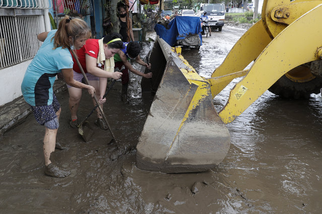 Residents use shovels to push mud inside a bulldozer as they try to clear out their area after floodwaters caused by Typhoon Goni rose inside their village in Batangas city, Batangas province, south of Manila, Philippines on Monday, November 2, 2020. Super typhoon Goni left wide destruction as it slammed into the eastern Philippines with ferocious winds early Sunday and about a million people have been evacuated in its projected path. (Photo by Aaron Favila/AP Photo)