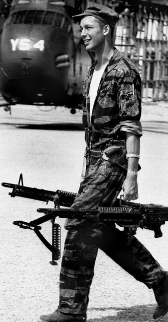 Yankee Papa 13 crew chief James Farley carries M-60 machine guns to the helicopter. (Photo by Larry Burrows/Time & Life Pictures)