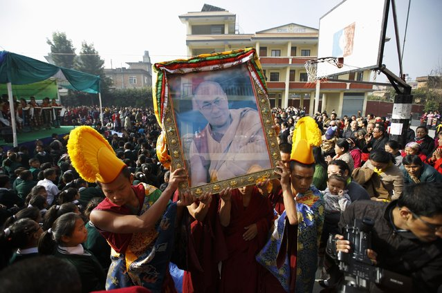 Tibetan monks carry a portrait of exiled Tibetan spiritual leader, the Dalai Lama, during a function organised by the Tibetan Refugee Community in Nepal, commemorating the 25th Anniversary of the Nobel Peace Prize conferment to exiled Tibetan spiritual leader Dalai Lama and the 66th International Human Rights Day in Kathmandu December 10, 2014. (Photo by Navesh Chitrakar/Reuters)