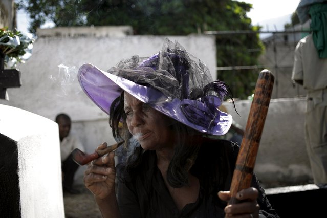A woman smokes during Day of the Dead celebrations at the National Cemetery in Port-au-Prince, Haiti, November 1, 2015. (Photo by Andres Martinez Casares/Reuters)