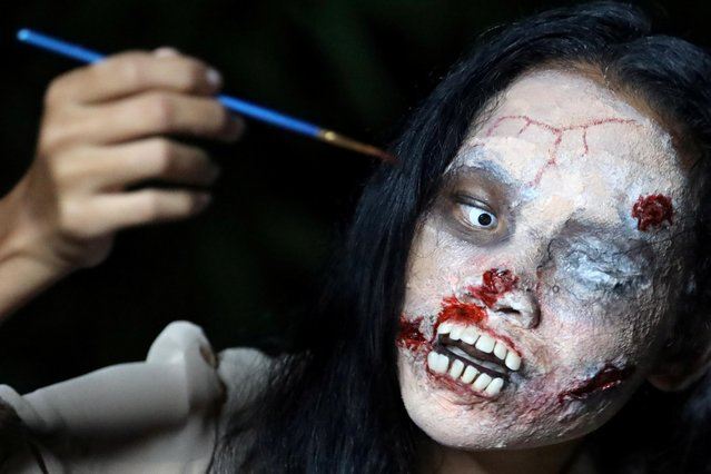 Online clothes seller, Kanittha Thongnak, 32, applies zombie makeup before she starts livestreaming selling dead people's clothes in Bangkok, Thailand on October 10, 2020. (Photo by Jiraporn Kuhakan/Reuters)