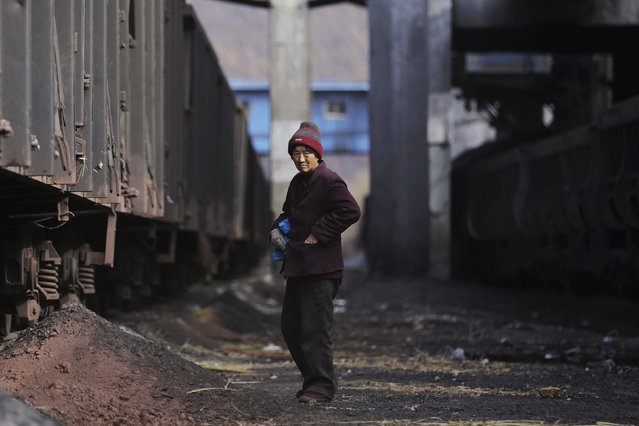 A rag-and-bone woman stands next to carriages of a coal train outside a coal mine of the state-owned Longmay Group on the outskirts of Jixi, in Heilongjiang province, China, October 22, 2015. (Photo by Jason Lee/Reuters)