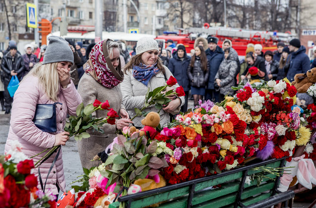 People lay flowers for the victims of a fire in a multi-story shopping center in the Siberian city of Kemerovo, about 3,000 kilometers (1,900 miles) east of Moscow, Russia, Monday, March 26, 2018. Russian officials say a fire at a shopping mall in a Siberian city has killed over 50 people. The Ekho Mosvky radio station quoted witnesses who said the fire alarm did not go off and that the staff in the mall in Kemerovo did not organize the evacuation. (Photo by AP Photo)