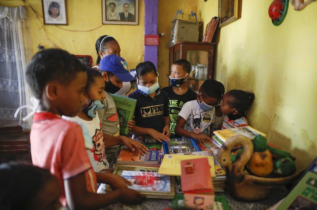 "Children look at books donated by the Venezuelan charity, ""Feed the Solidarity"", at a home where children are tutored by volunteers, in the San Agustin neighborhood of Caracas, Venezuela, Wednesday, November 3, 2020. The U.N. children's agency UNICEF says that the COVID-19 has deprived 97% of children in Latin America and the Caribbean of their normal schooling over seven months since the continent's first COVID-19 cases were discovered. (Photo by Ariana Cubillos/AP Photo)"