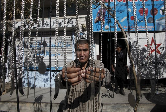 A man displays necklaces with religious motif for sale at his makeshift stall ahead of the Shi'ite Muslim festival of Ashura in Quetta, Pakistan, October 20, 2015. Ashura, which falls on the 10th day of the Islamic month of Muharram, commemorates the death of Imam Hussein, grandson of Prophet Mohammad, who was killed in the 7th century battle of Kerbala. (Photo by Naseer Ahmed/Reuters)