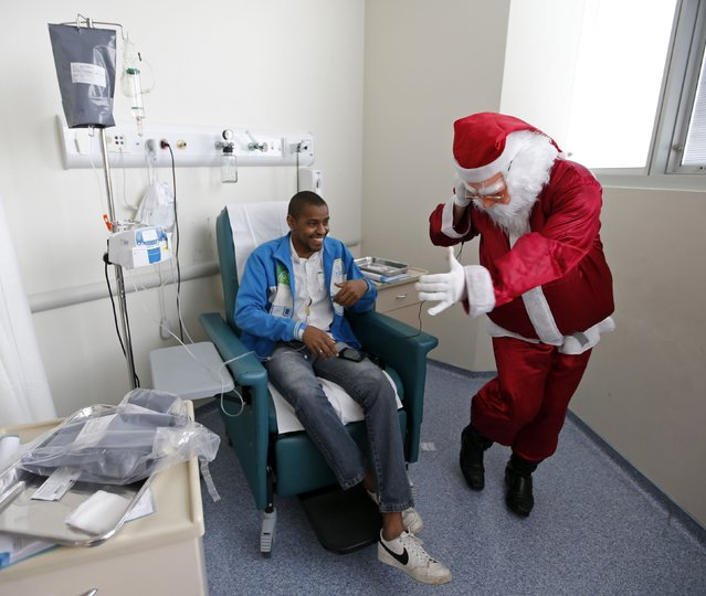 A man dressed as Santa Claus dances while listening to music on headphones borrowed from a cancer patient (L) undergoing chemotherapy in the Cancer Institute in Sao Paulo December 19, 2014. (Photo by Paulo Whitaker/Reuters)