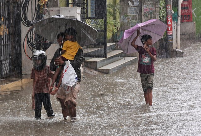 Indians wade through a waterlogged street as it rains in Hyderabad, India, Wednesday, September 21, 2016. Monsoon season in India begins in June and ends in October. (Photo by Mahesh Kumar A./AP Photo)