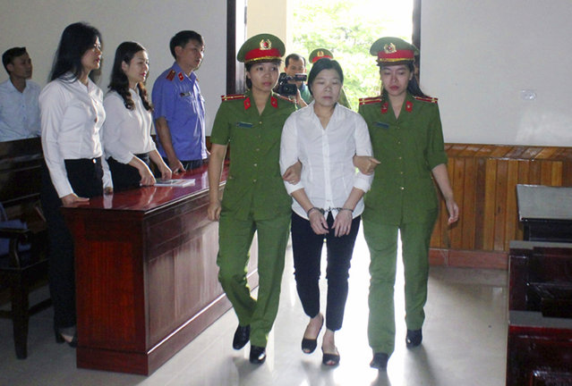Activist Tran Thi Xuan is escorted into a court room in Ha Tinh province, Vietnam, Thursday, April 12, 2018. Xuan was convicted of attempting to overthrow the government at half-day trial and sentenced to nine years in prison. (Photo by Cong Tuong/Vietnam News Agency via AP Photo)