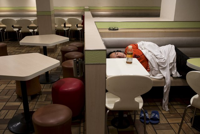 A man sleeps at a 24-hour McDonald's restaurant in Hong Kong, China November 10, 2015. A large number of homeless people sleeping on the street has long been been a problem in Hong Kong mainly due to its high rent and soaring property. In recent years, McDonald's 24-hour fast food shops opening all over the city have become popular alternatives for people, know as McRefugees or McSleepers, to spend the night in a safer and more comfortable way than on the street. Picture taken on November 10, 2015. REUTERS/Tyrone Siu