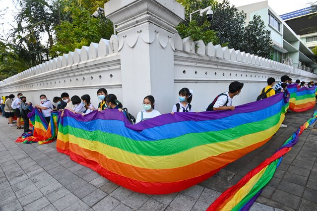 "Students hold up a rainbow flag in support of the LGBTQ movement during a ""Bad Student"" protest outside the Ministry of Education in Bangkok on December 1, 2020. (Photo by Mladen Antonov/AFP Photo)"