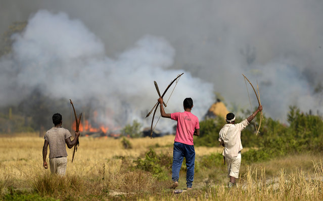 Tribal men with their bows and arrows watch towards houses belonging to Bodo community people after they were set on fire in retaliation in Tenganala village in Sonitpur district of Assam state, India, 24 December 2014. Police said on 24 December the number of villagers killed by insurgents in north-east India has risen to more than 60. (Photo by EPA/Stringer)