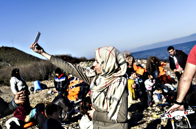 A woman takes a selfie after arriving, along with other migrants and refugees, on the Greek island of Lesbos by crossing the Aegean Sea from Turkey on November 13, 2015. EU leaders on November 12 struck an aid-for-cooperation deal with Africa and proposed a summit this year with Turkey in a two-front push with wary partners to tackle an unprecedented migrant crisis. (Photo by Bulent Kilic/AFP Photo)