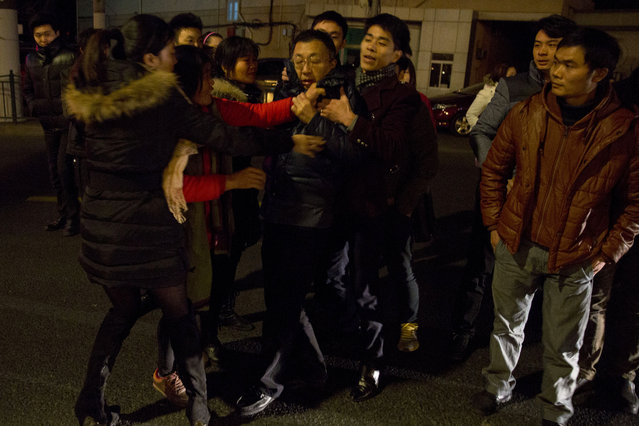Relatives of victims of a deadly stampede, angered by the lack of information, drag a municipal officer, center onto the road demanding answers in Shanghai, China, Thursday, January 1, 2015. (Photo by Ng Han Guan/AP Photo)