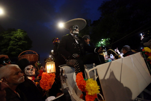 "People with their faces painted to look like the popular Mexican figure called ""Catrina"" and others painted as skulls take part in a procession to celebrate the upcoming annual Day of the Dead on November 1 and 2, at Reforma avenue, in Mexico City, Mexico, October 23, 2016. (Photo by Edgard Garrido/Reuters)"