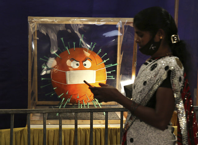 A woman wears a face mask on her chin and walks past a cake depicting the coronavirus on display at the annual cake show organized as part of new year celebrations in Bengaluru, India, Tuesday, December 29, 2020. India's confirmed coronavirus cases have crossed 10 million with new infections dipping to their lowest levels in three months, as the country prepares for a massive COVID-19 vaccination in the new year. (Photo by Aijaz Rahi/AP Photo)