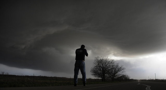 Storm chaser Brad Mack from Buena Park California videotapes a rotating supercell storm west of Newcastle, Texas April 9, 2013. (Photo by Gene Blevins/Reuters)
