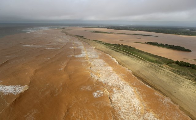 A general view the sea (L) and Rio Doce (Doce River), which was flooded with mud after a dam owned by Vale SA and BHP Billiton Ltd burst, on the coast of Espirito Santo in Povoacao Village, Brazil, November 22, 2015. (Photo by Ricardo Moraes/Reuters)