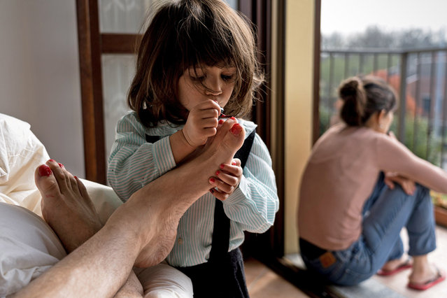"Life in lockdown: Schoolteacher Marzio Toniolo, 35, takes a picture of his two-year-old daughter Bianca painting his toenails as they while away time at home in San Fiorano, one of the original ""red zone"" towns in northern Italy that has now been extended to the whole country, as his wife, Bianca's mum Chiara Zuddas looks out from their balcony, March 20, 2020. Toniolo has been documenting how his family has dealt with being under quarantine since it began for them in February. (Photo by Marzio Toniolo via Reuters)"