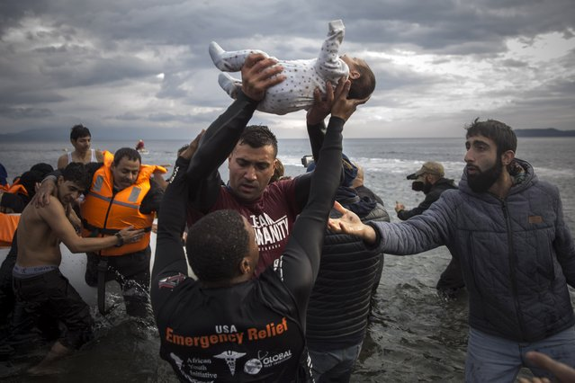 A volunteer holds up a baby as others help migrants and refugees to disembark from a dinghy after their arrival from the Turkish coast to the Greek island of Lesbos, Wednesday, November 25, 2015. (Santi Palacios/AP Photo)