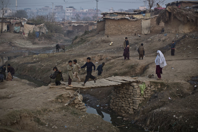 Children run on a wooden bridge over a stream of rain water and sewage in a poor neighborhood that hosts Afghan refugees and internally displaced Pakistanis from tribal areas, on the outskirts of Islamabad, Pakistan, Sunday, December 28, 2014. (Photo by Muhammed Muheisen/AP Photo)