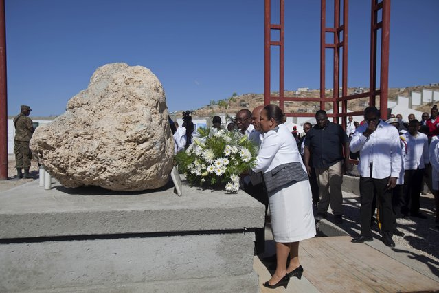 Haiti's President Michel Martelly, center, and Haiti's first lady Sophia Martelly, place a floral arrangement during the memorial service for victims of the January 2010 earthquake, at Titanyen, a mass burial site north of Port-au-Prince, Haiti, Monday, January 12, 2015. (Photo by Dieu Nalio Chery/AP Photo)