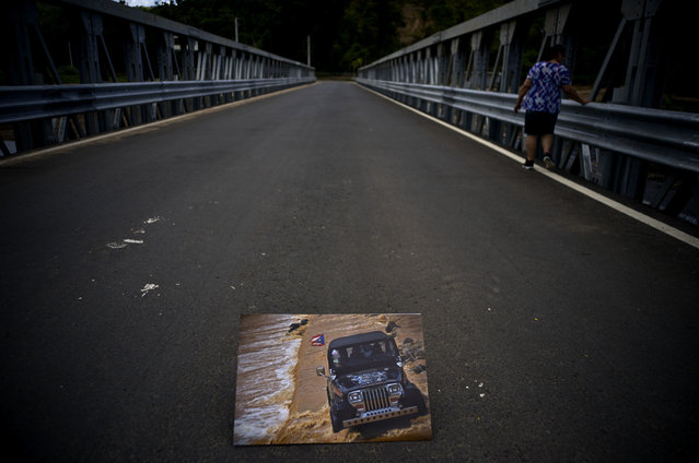 A printed photograph of a jeep crossing a river on October 7, 2017 sits placed on a new bridge that stands above the spot where the print was taken after Hurricane Maria washed out the old bridge in the San Lorenzo neighborhood of Morovis, Puerto Rico, May 26, 2018. People on both sides of the bridge were left stranded when it collapsed, turning a 45 minute commute to the other side into a three hour oddesy. (Photo by Ramon Espinosa/AP Photo)