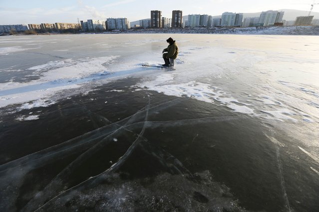 A man fishes through an ice hole on the frozen Abakan Bay of the Yenisei River in Russia's Siberian city of Krasnoyarsk January 11, 2015. (Photo by Ilya Naymushin/Reuters)
