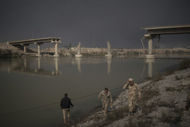 Iraqi army soldiers walk by the river near a bridge destroyed by an airstrike in Qayara, south of Mosul, Iraq, Saturday, November 5, 2016. Islamic State fighters launched counterattacks in the thin strip of territory Iraqi special forces have recaptured in eastern Mosul, highlighting the challenges ahead as the battle moves into more densely populated neighborhoods where coalition air power must be used more selectively. (Photo by Felipe Dana/AP Photo)