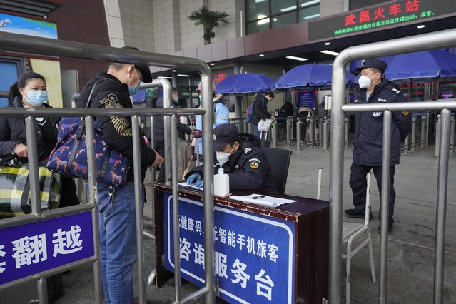 Travelers are screened before entering the Wuchang train station at the start of the annual Lunar New Year travel in Wuhan in central China's Hubei province on Thursday, January 28, 2021. Efforts to dissuade Chinese from traveling for Lunar New Year appeared to be working as Beijing's main train station was largely quiet and estimates of passenger totals were smaller than in past years. (Photo by Ng Han Guan/AP Photo)