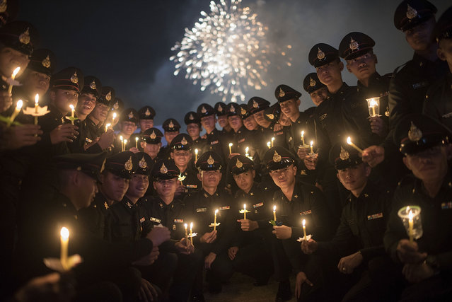 Thai policemen pose for a picture during a massive candle light ceremony for King's birthday at Sanam Luang on December 5, 2015 in Bangkok, Thailand. The world's longest-reigning monarch, King Bhumibol Adulyadej's health is closely watched as he is kept in hospital now and hasn't been publicly seen in weeks. The Thai King has been considered the most unifying symbol for a country that has seen increased political divisions and violence. (Photo by Borja Sanchez-Trillo/Getty Images)